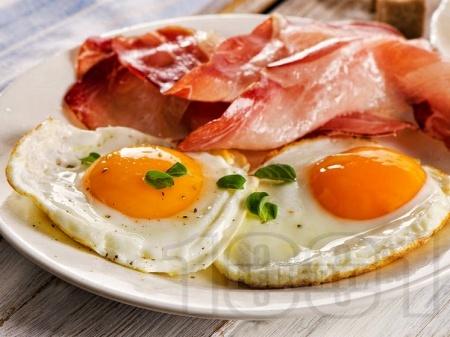 Пържени яйца на очи с бекон поднесени с пържени филийки - снимка на рецептата